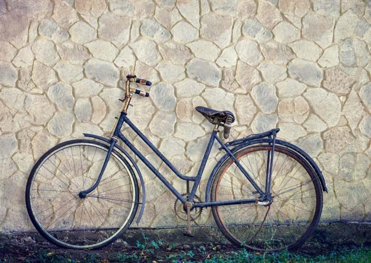 Vélo posé sur un mur en pierre reconstituée mathios fieldstone clair