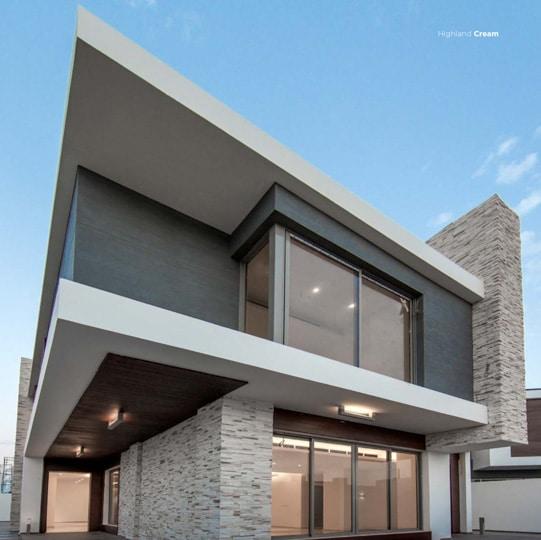 Contre plongée d'une maison moderne avec pants de murs en pierre de parement mathios highland clair