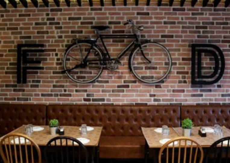 Intérieur de restaurant avec un pant de mur en pierre de parement mathios masterbrick