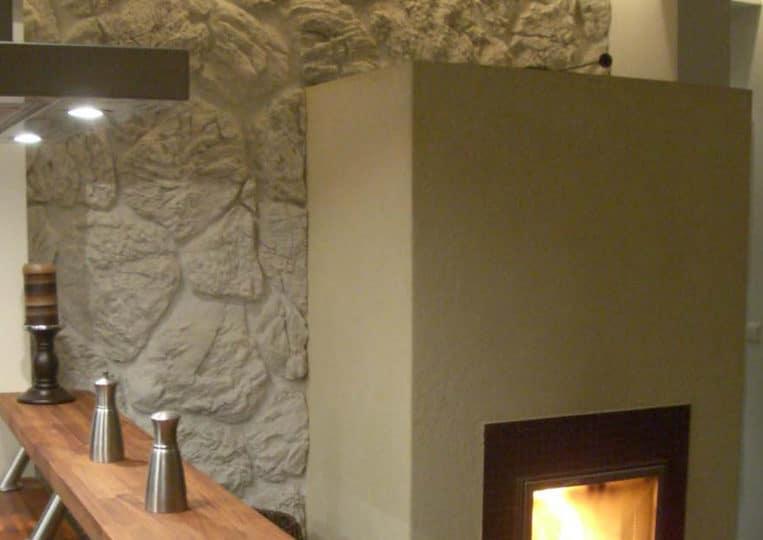 Cheminée intérieure avec un pant de mur en pierre de parement mathios terra clair