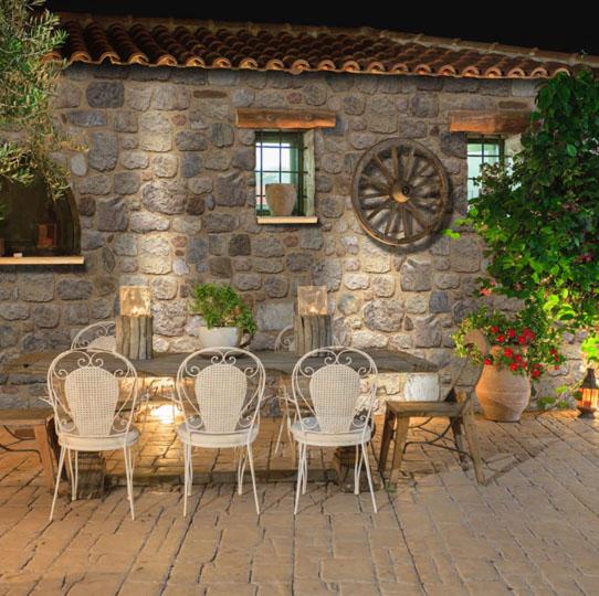 Terasse extérieure avec table à manger et mur en pierre reconstituée mathios arcadian