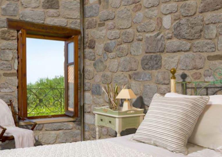 Chambre à coucher avec des murs en pierre reconstituée mathios arcadian