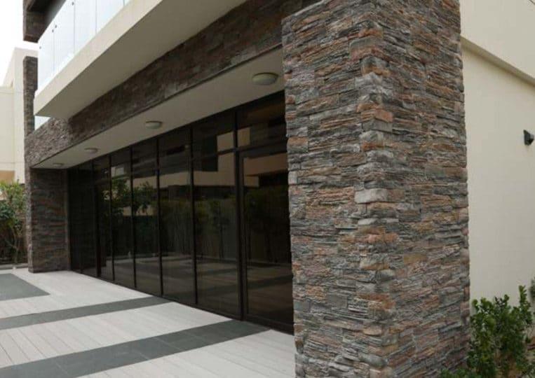 Entrée de magasin avec une devanture en pierre reconstituée mathios bretagne grise et portes coulissantes