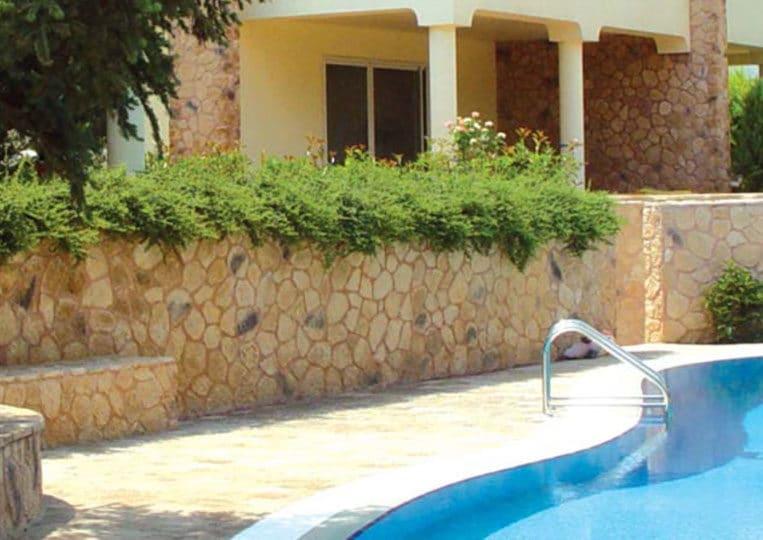 Bord de piscine et muret avec réalisé en pierre reconstituée mathios ekali clair
