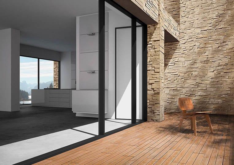 Porte donnant sur une terasse extérieure avec un pant de mur en pierre de parement acl royal sable