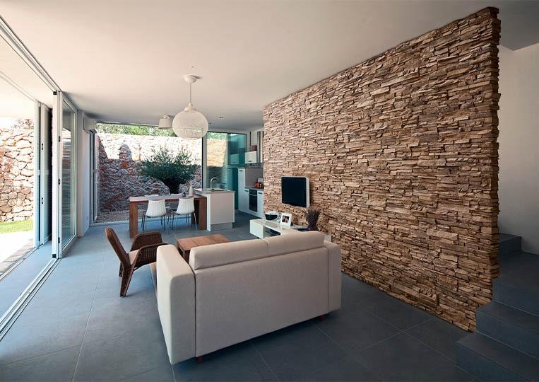 salon intérieur avec un pant de mur en pierre de parement acl siena café