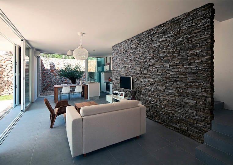 salon intérieur avec un pant de mur en pierre de parement acl siena anthracite