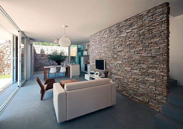 salon intérieur avec un pant de mur en pierre de parement acl siena gris
