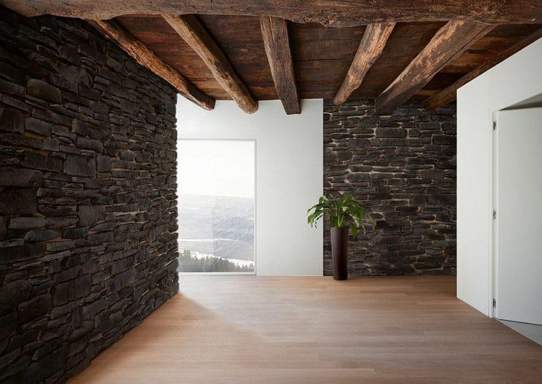 Intérieur d'une pièce avec des murs en pierre de parement acl teira anthracite