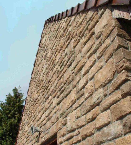 Contre plongée d'une maison avec un pant de mur en pierre reconstituée pietre d'arredo granada