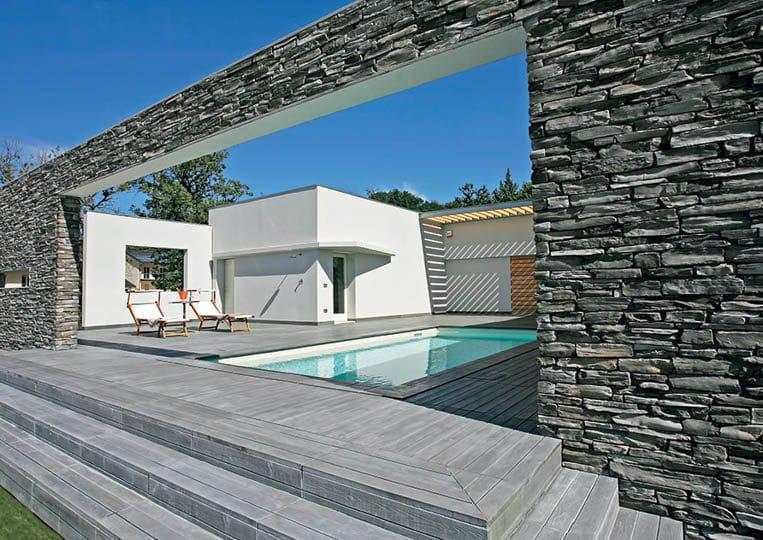 Terasse extérieure avec piscine et murs en pierres reconstituées pietre d'arredo olkaria