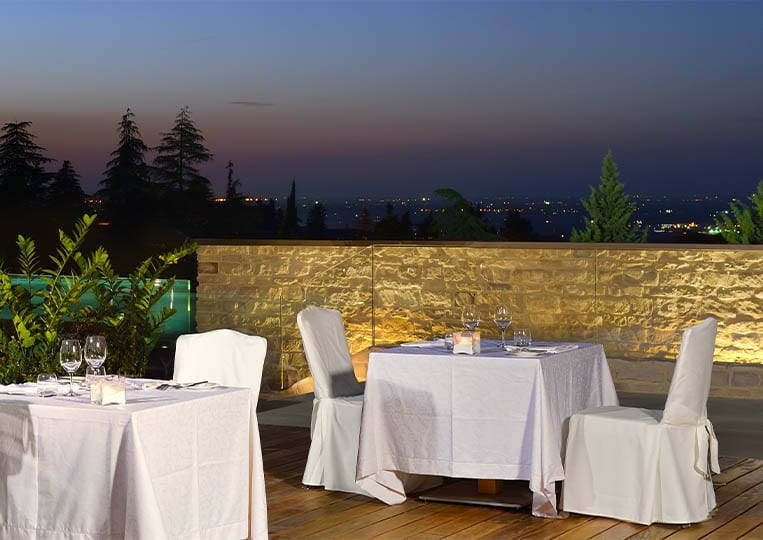 Terasse extérieure d'un restaurant avec des tables et un muret construit en pierre reconstituée pietre d'arredo taos