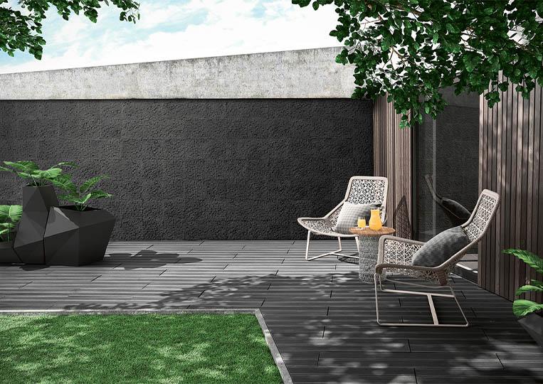 Terasse extérieure de jardin avec un pant de mur en pierre reconstituée couleur anthracite acl cubus