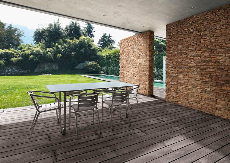 Terasse extérieure couverte avec table à manger et pant de mur en pierre reconstituée acl luna café