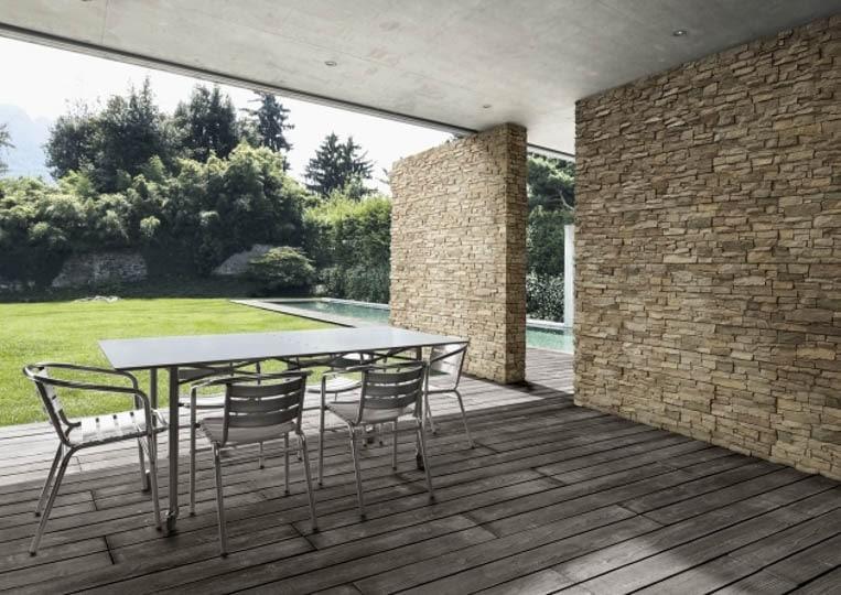 Terasse extérieure couverte avec table à manger et pant de mur en pierre reconstituée acl luna sable