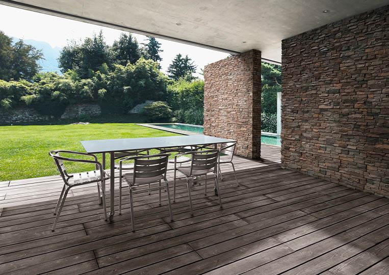 Terasse extérieure couverte avec table à manger et pant de mur en pierre reconstituée acl luna café foncé