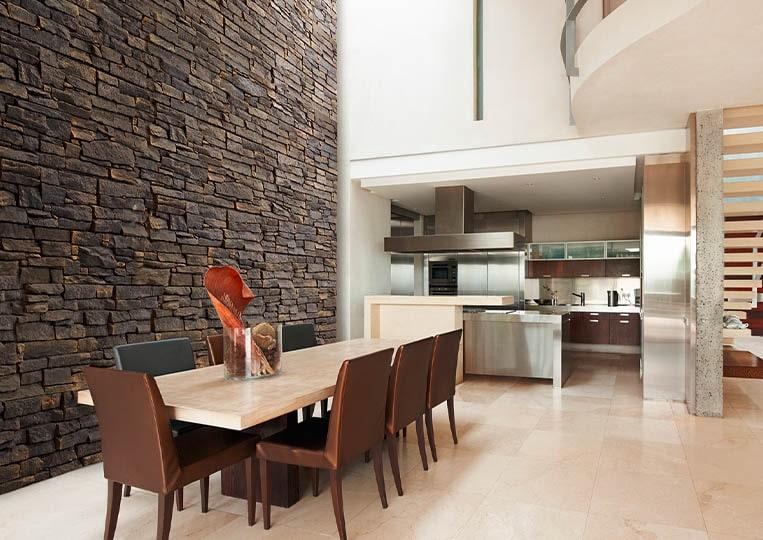 Salle à manger avec un grand pant de mur en pierre reconstituée acl luna café foncé