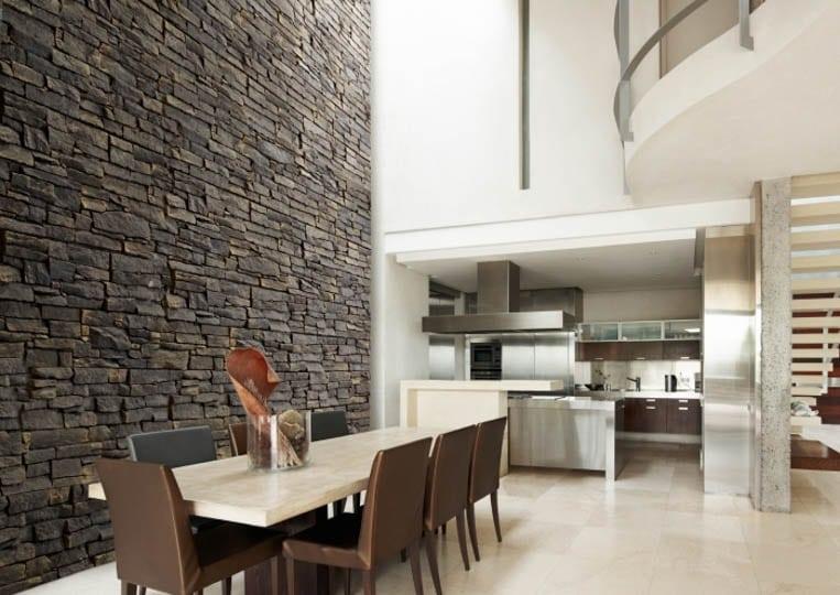 Salle à manger avec un grand pant de mur en pierre reconstituée acl luna gris foncé