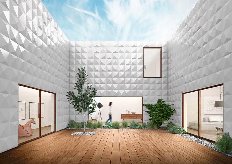 Vue en contre plongée d'une terasse extérieure entourée de mur en pierre reconstituée couleur clair acl prisma