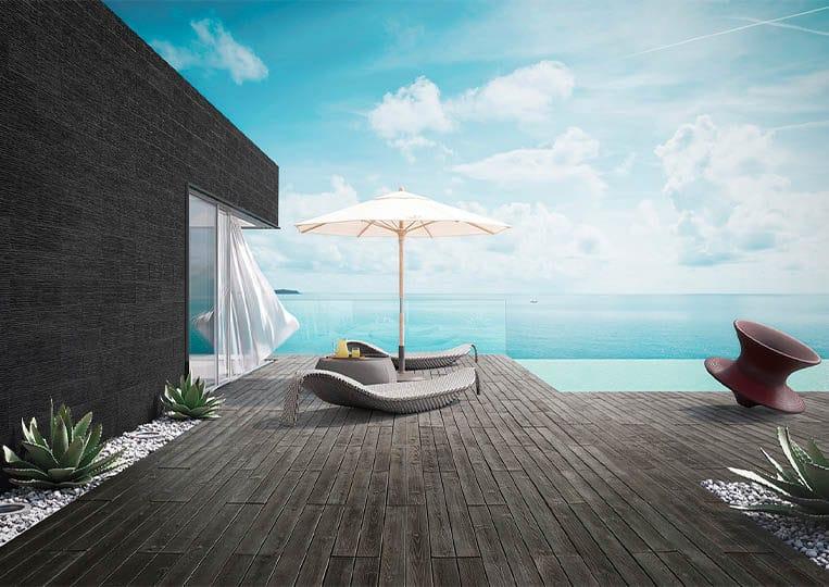 Terasse extérieure vue sur mer, transat, parasol et pant de mur en pierre reconstituée couleur noir acl riscado