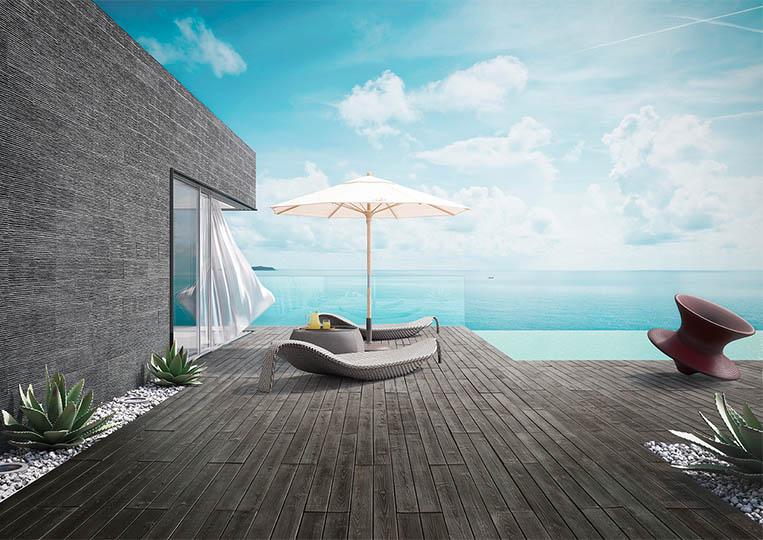 Terasse extérieure vue sur mer, transat, parasol et pant de mur en pierre reconstituée couleur gris acl riscado