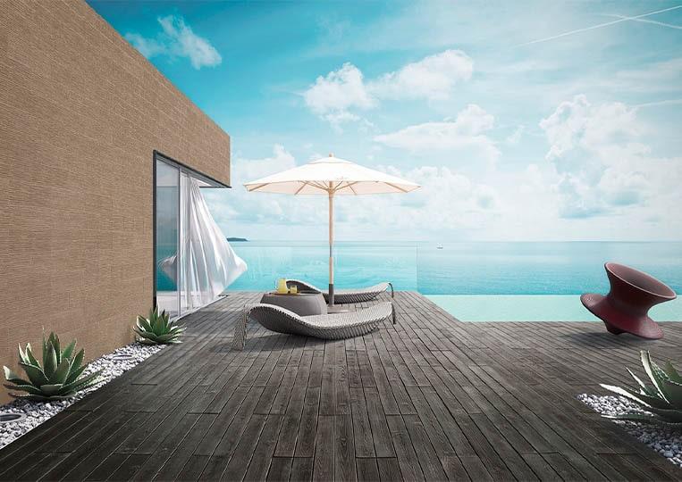 Terasse extérieure vue sur mer, transat, parasol et pant de mur en pierre reconstituée couleur café acl riscado