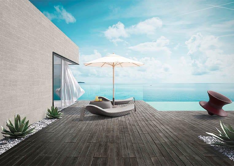 Terasse extérieure vue sur mer, transat, parasol et pant de mur en pierre reconstituée couleur clair acl riscado