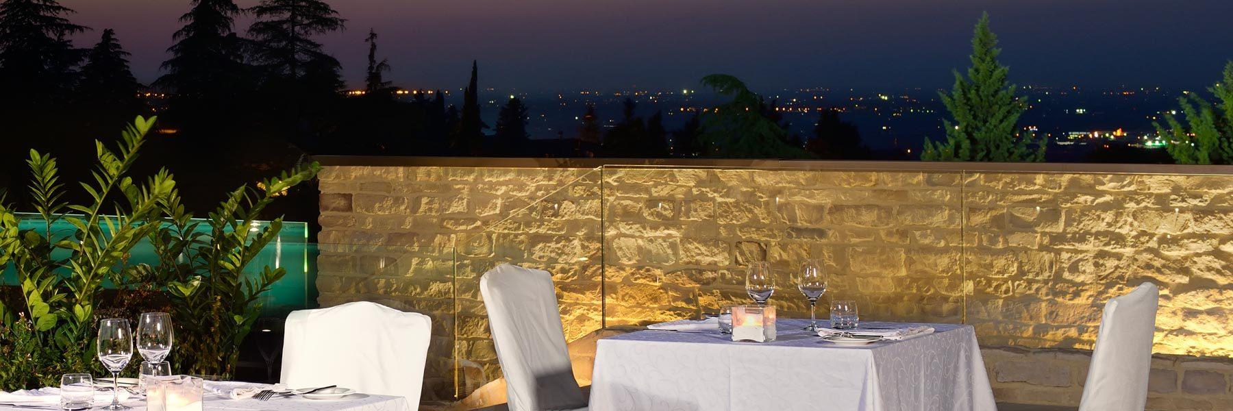 Terrasse d'un restaurant avec des tables et un pan de mur en pierre reconstituée Pietre d'Arredo taos